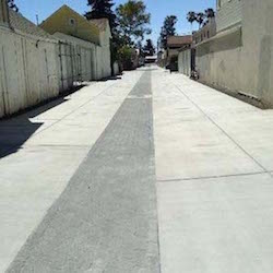 A long wide alley way recently paved with permeable pavers running along the middle